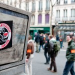 An anti-fascist sticker on cabin phone in front of the security members