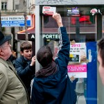 Young people of the demonstration removing the Antifascist sticker before sticking their own