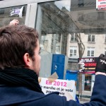 Young people of the demonstration removing the Antifascist sticker before sticking theire own
